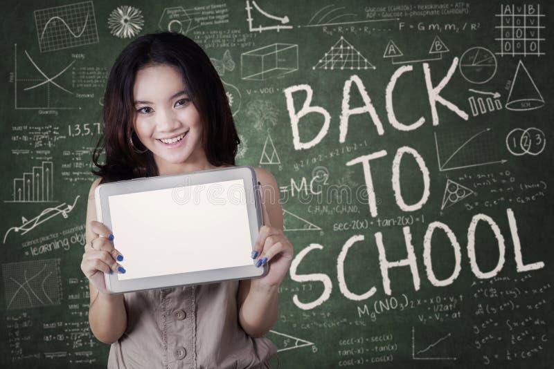 Écolière attirante avec le comprimé dans la classe photographie stock libre de droits