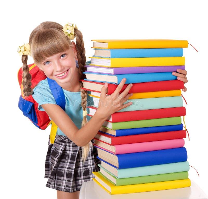 Écolière avec la pile de fixation de sac à dos des livres. photo libre de droits