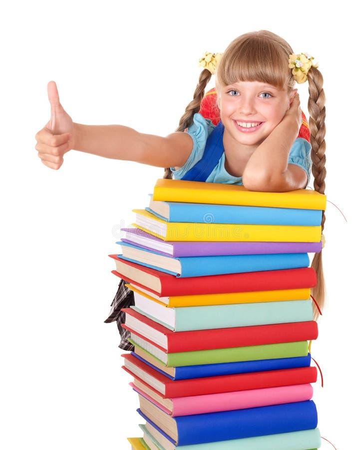 Écolière avec la pile des livres affichant le pouce vers le haut. image libre de droits