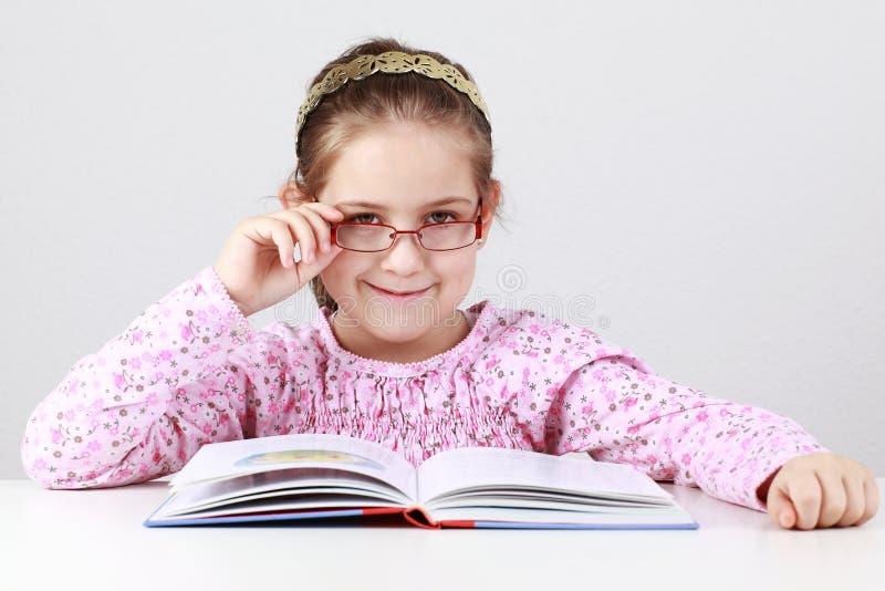 Écolière avec le livre de relevé en verre photo libre de droits