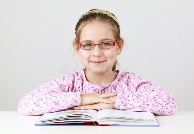 Écolière avec le livre de relevé en verre image stock