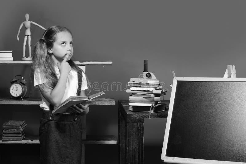 Écolière avec le visage réfléchi dans sa salle de classe Les prises de fille ouvrent le livre et se tiennent prêt le tableau noir images stock