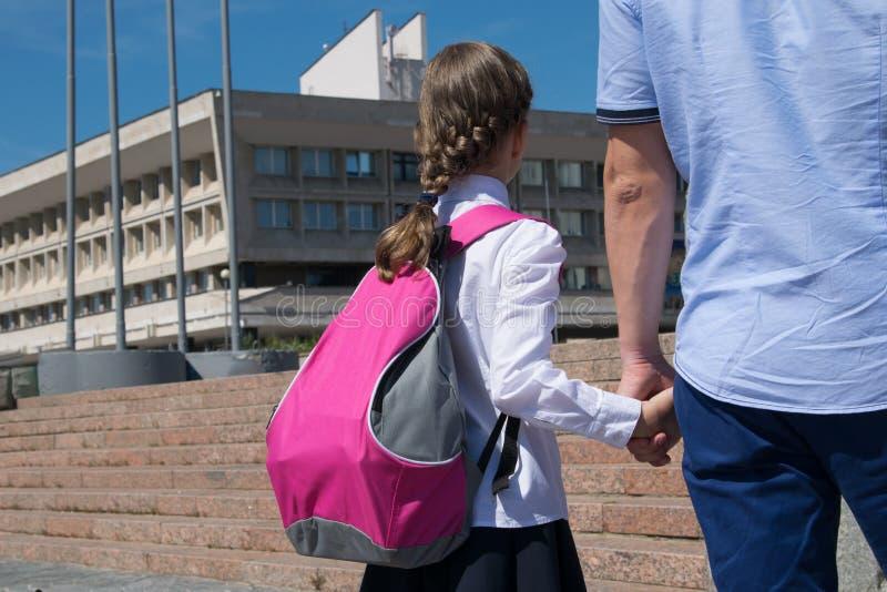 Écolière, avec une serviette rose, tenant une main du ` s de papa, sur son chemin sur l'école photo libre de droits