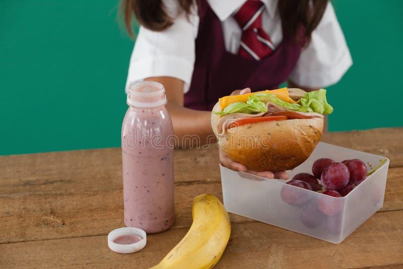 Écolière ayant le sandwich images stock