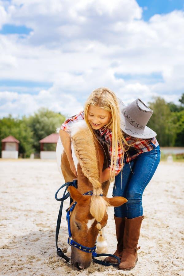 Écolière bienfaisante jouant avec le petit poney mignon avec la tresse photo libre de droits