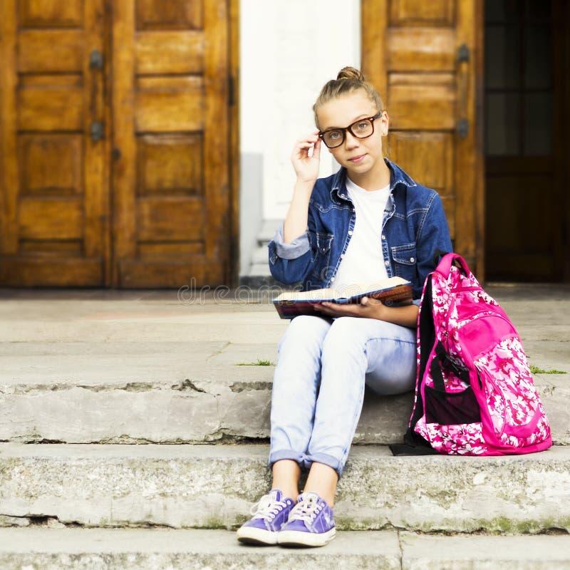 Écolière blonde mignonne de fille lisant un livre tout en se reposant près de l'école Éducation photos libres de droits