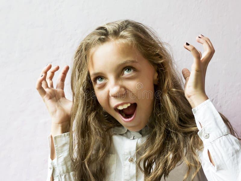 Écolière blonde mignonne de fille sur un fond clair Éducation Émotions et sentiments photographie stock libre de droits
