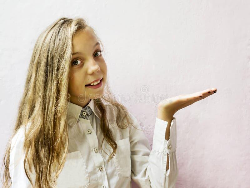Écolière blonde mignonne de fille sur un fond clair Éducation image stock