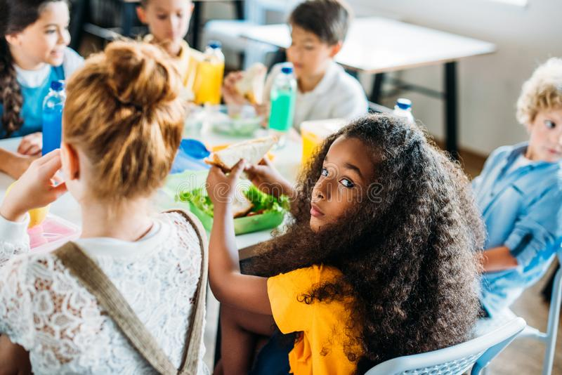 écolière d'afro-américain prenant le déjeuner à la cafétéria de l'école avec ses camarades de classe et regard photographie stock libre de droits