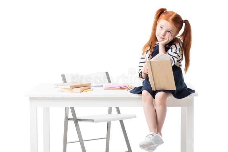 écolière d'une chevelure rouge songeuse tenant le livre tout en se reposant sur la table et regardant loin photos libres de droits