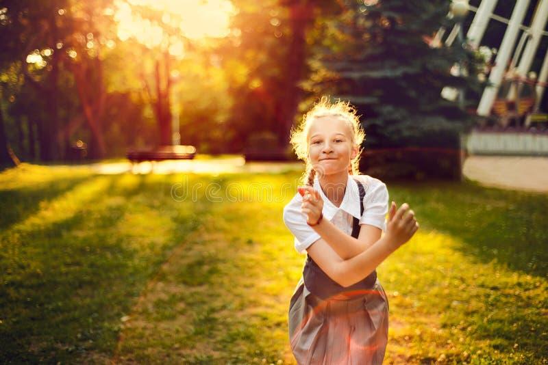 Écolière dans l'uniforme avec la danse joyeuse de tresses au coucher du soleil i photographie stock libre de droits