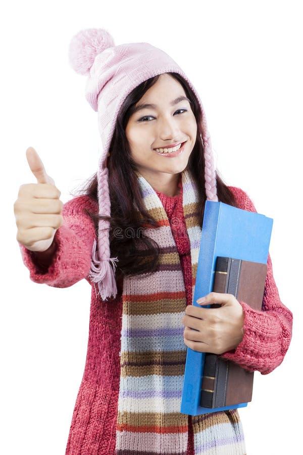 Écolière dans l'usage d'hiver donnant des pouces- photo stock