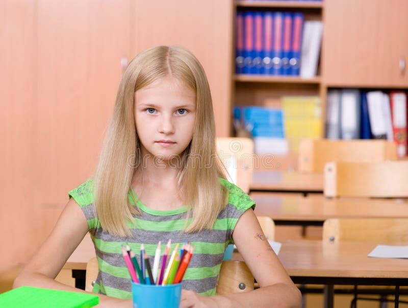 écolière dans la salle de classe regarder l'appareil-photo photo stock