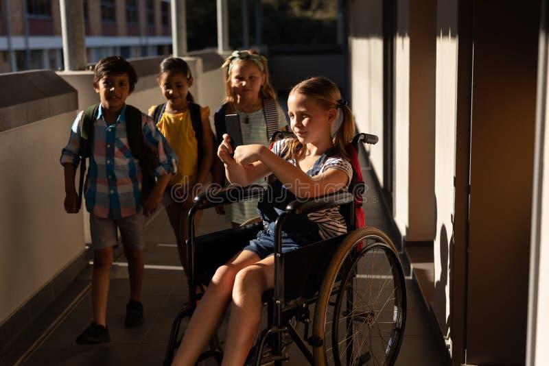 Écolière de débronchement à l'aide du smartphone dans le couloir images stock