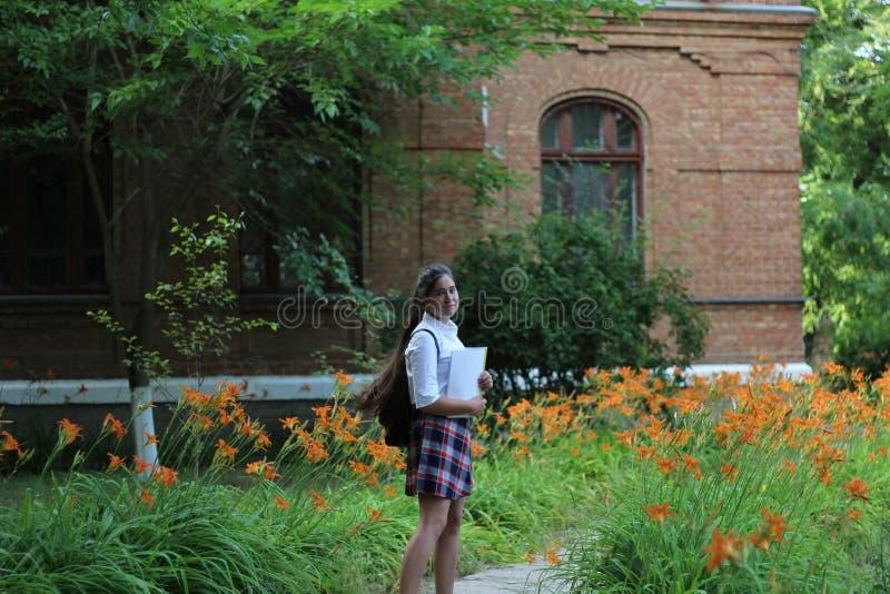 Écolière de fille avec un dossier dans des ses mains photo libre de droits