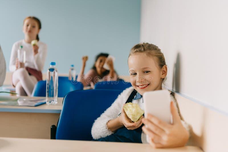 écolière de l'adolescence heureuse prenant le selfie au moment de salle de classe images libres de droits