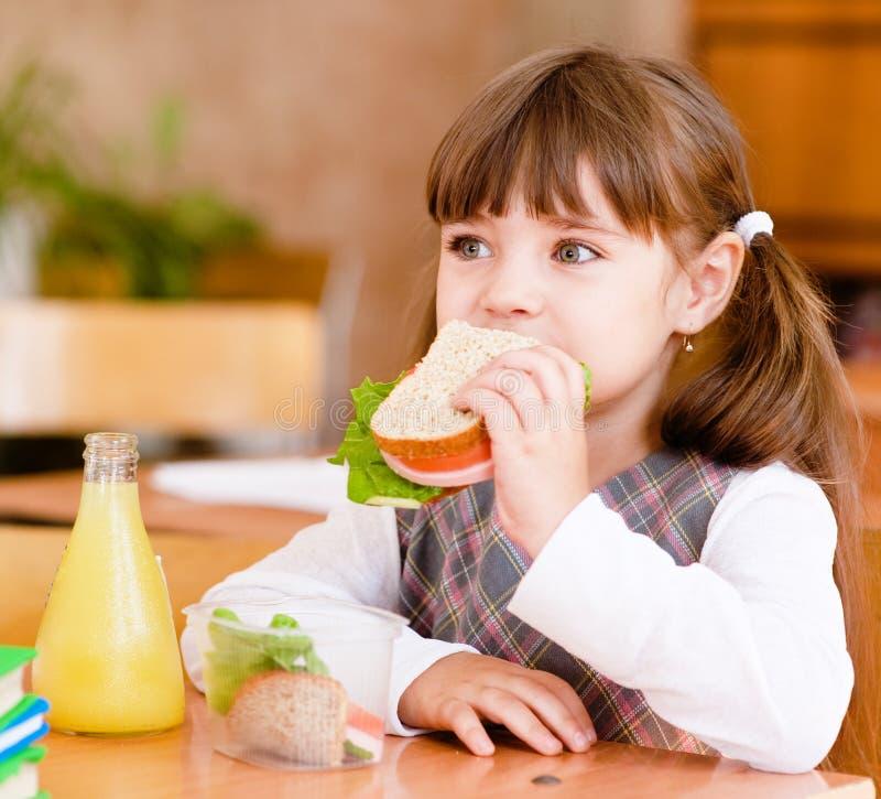 Écolière de portrait tout en prenant le déjeuner pendant photos libres de droits