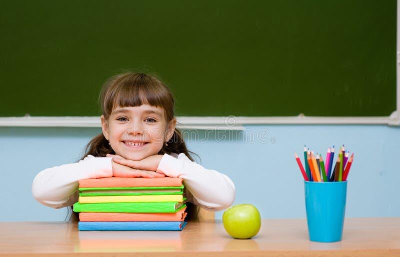 Écolière de sourire dans la salle de classe sur le fond du tableau photos libres de droits