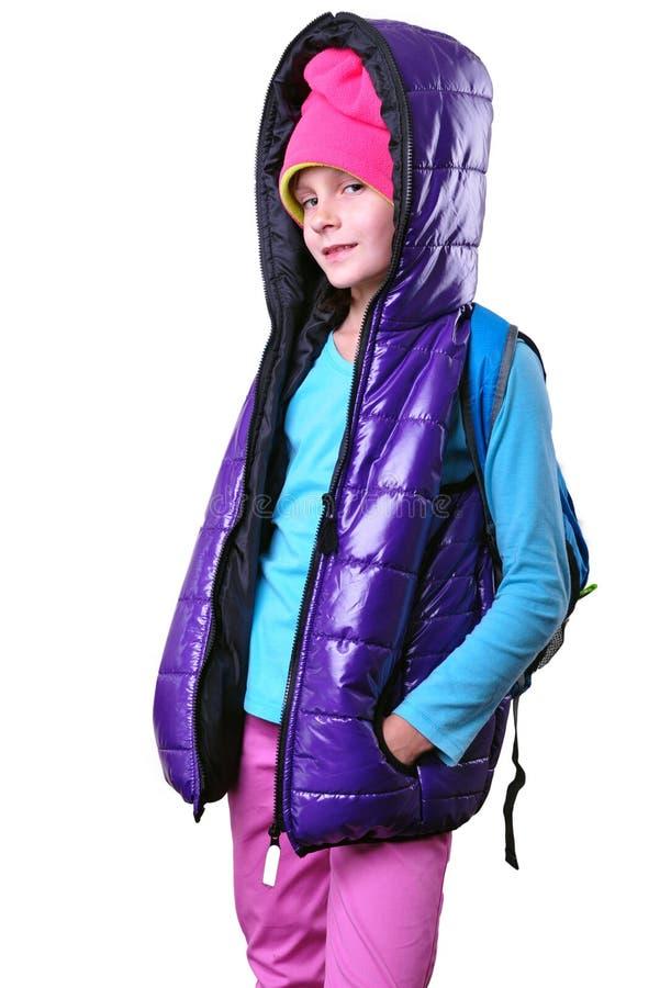 Écolière de sourire heureuse avec le sac à dos d'isolement au-dessus du blanc image stock