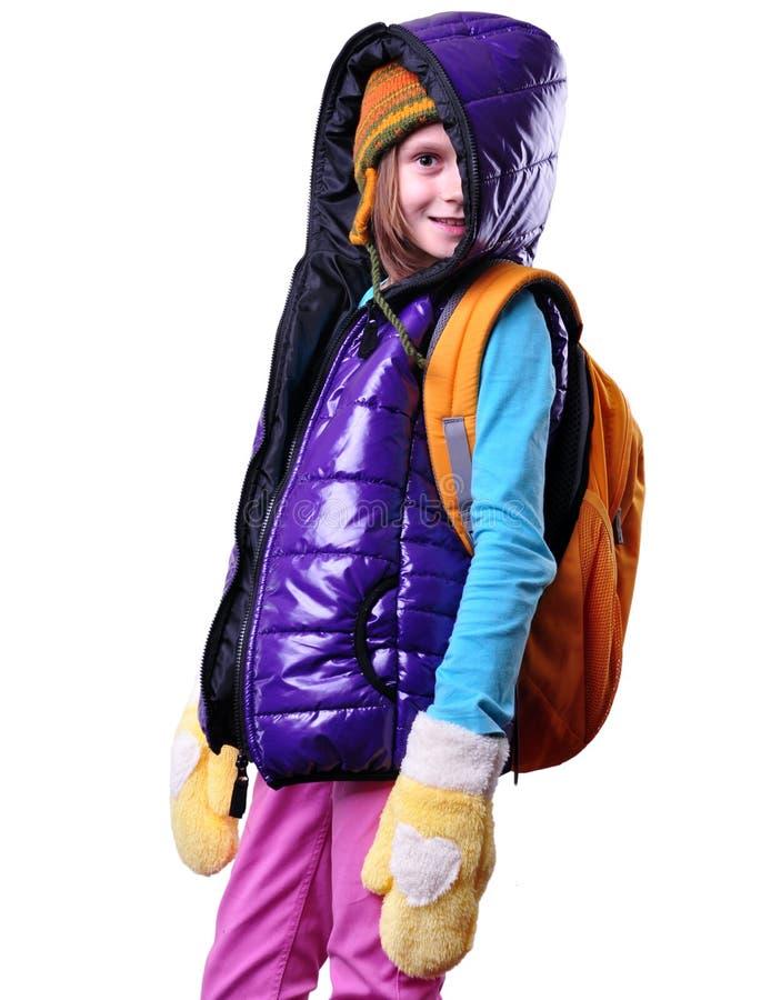 Écolière de sourire heureuse avec le sac à dos d'isolement au-dessus du blanc photographie stock libre de droits