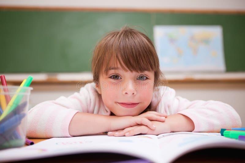 Écolière de sourire se penchant sur un bureau image libre de droits
