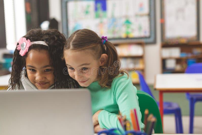 Écolière deux ayant un sourire affecté tandis qu'ils travaillant sur leur ordinateur portable photo libre de droits