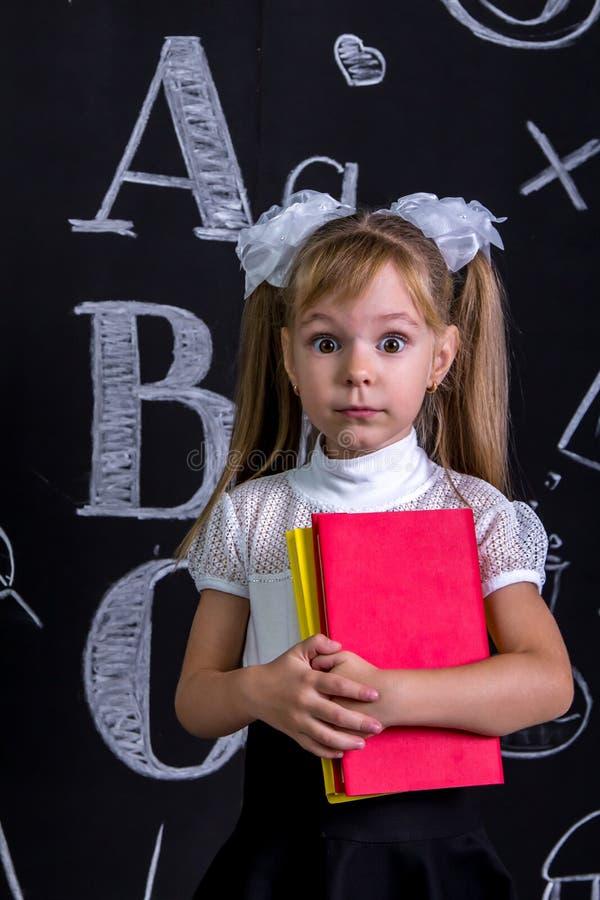 Écolière effrayée se tenant avant le tableau comme fond avec quelques livres les étreignant Photo de portrait photo libre de droits