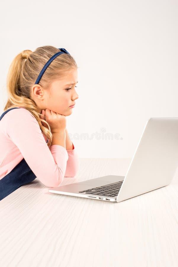 Écolière en verres se reposant au bureau images stock