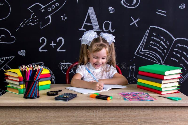 Écolière enthousiaste et heureuse s'asseyant au bureau avec des livres, fournitures scolaires, jugeant le stylo dans la main droi images stock