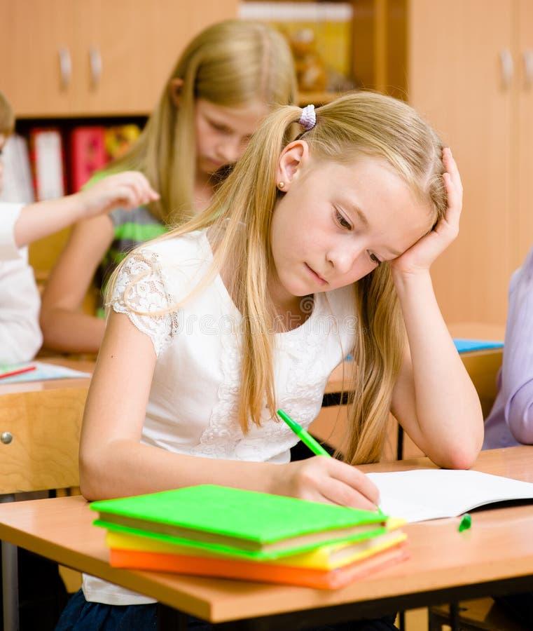 Écolière fatiguée dans la salle de classe photographie stock libre de droits