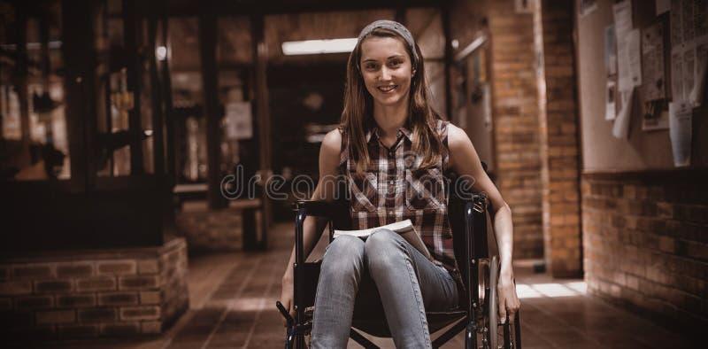 Écolière handicapée sur le fauteuil roulant dans le couloir à l'école illustration stock