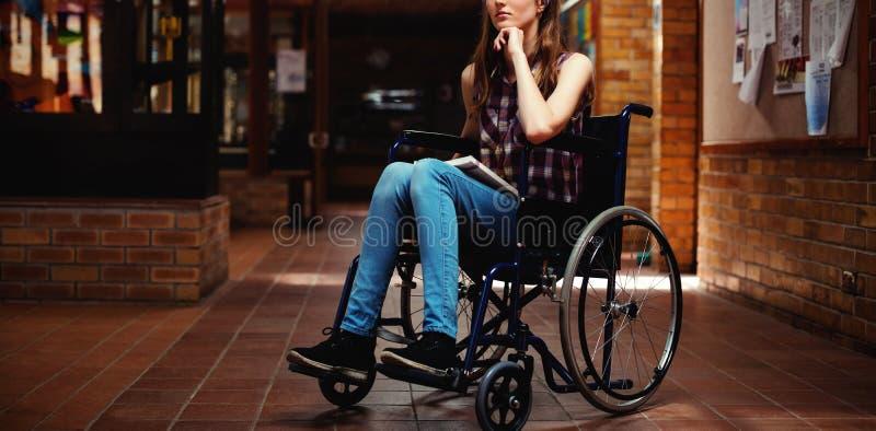Écolière handicapée sur le fauteuil roulant dans le couloir à l'école photographie stock libre de droits