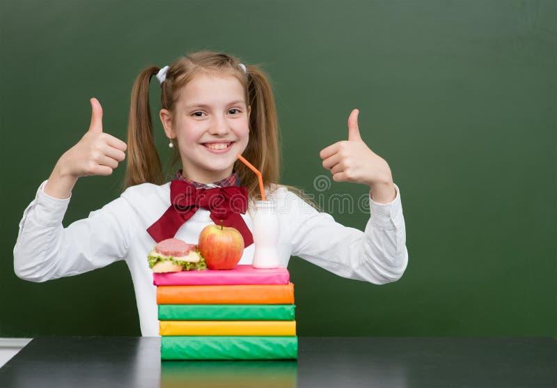 Écolière heureuse avec la nourriture dans la salle de classe montrant des pouces  image libre de droits