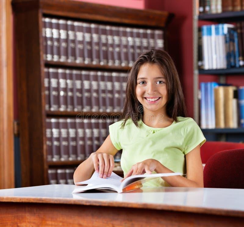 Écolière heureuse avec le livre photographie stock libre de droits