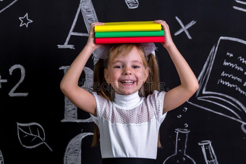 Écolière heureuse de sourire se tenant avant le tableau comme fond avec une pile des livres les tenant sur le dessus de photo stock