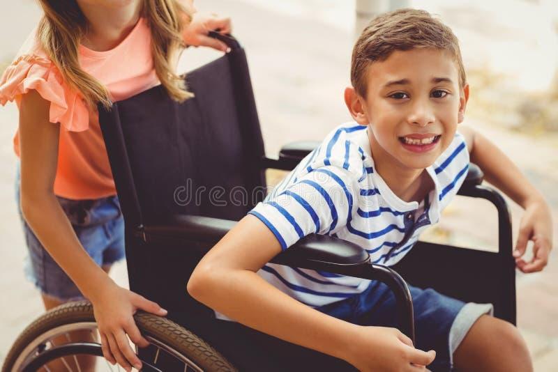 Écolière heureuse poussant un garçon sur le fauteuil roulant photo stock
