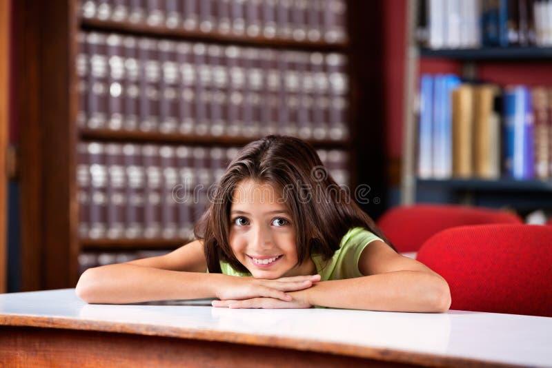 Écolière heureuse reposant Chin On Hands At Table dedans photographie stock
