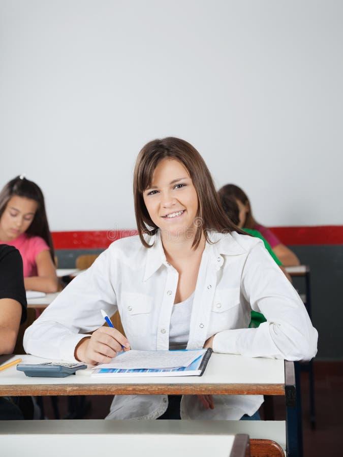 Écolière heureuse s'asseyant au bureau image libre de droits