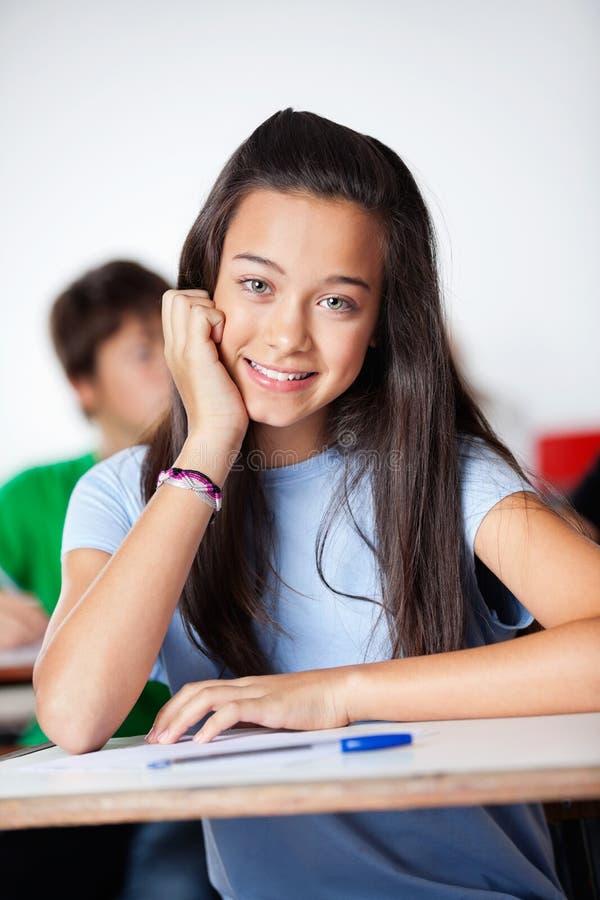 Écolière heureuse s'asseyant au bureau dans la salle de classe photographie stock libre de droits