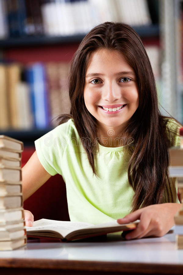 Écolière heureuse s'asseyant au Tableau dans la bibliothèque photo libre de droits
