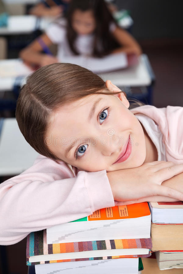 Écolière heureuse se penchant sur la pile de livres photos stock