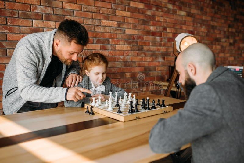 Écolière intelligente jouant aux échecs avec l'homme images stock