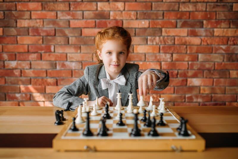 Écolière intelligente, joueur d'échecs à la table image libre de droits