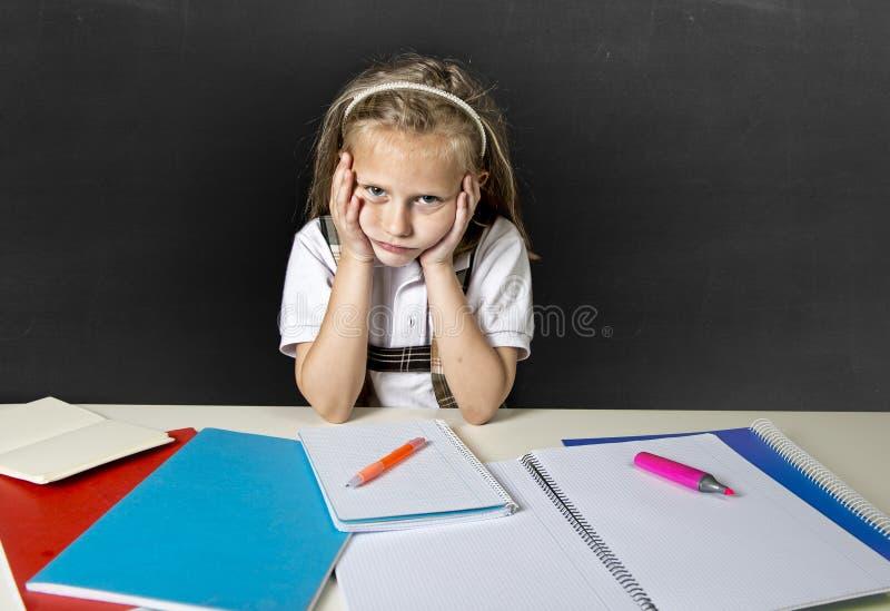 Écolière junior mignonne fatiguée avec les cheveux blonds se reposant dans l'effort fonctionnant faisant le travail semblant ennu photo stock