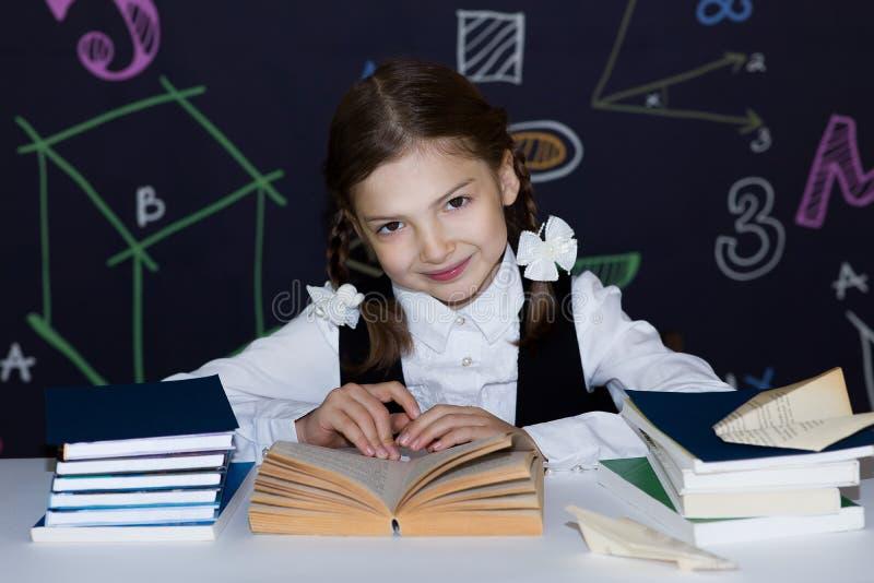 Écolière lisant un livre se reposant à la table, sur le fond du conseil pédagogique photos stock