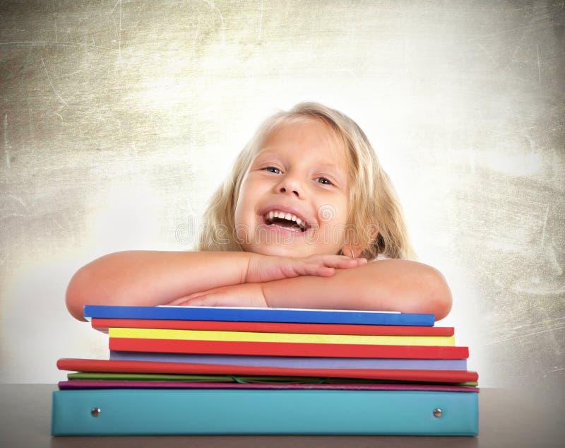 Écolière mignonne avec se reposer de cheveux blonds heureux sur le bureau riant et souriant photos stock