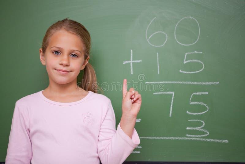 Écolière mignonne soulevant sa main photo libre de droits
