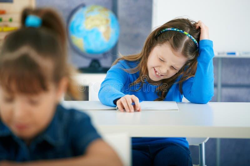 Écolière pensant dans la salle de classe photos stock