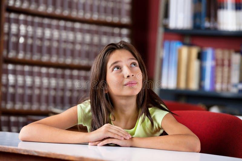 Écolière réfléchie recherchant dans la bibliothèque image stock