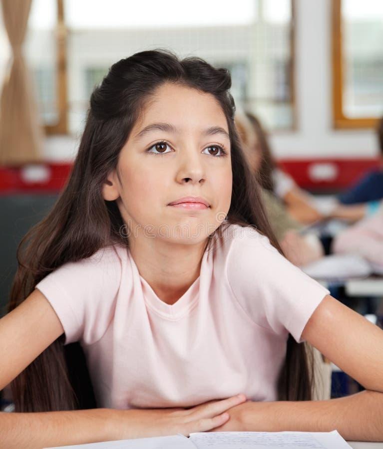 Écolière réfléchie semblant partie tout en se reposant photo libre de droits
